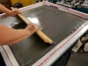 Image of screen printing as ink is pushed through screen