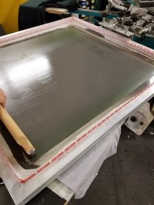 Image of screen printing as ink is pushed throught the screen